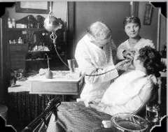 Dr. Sinton working on patient, circa 1915